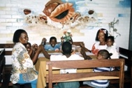 A family sitting under one of the murals at SOS Children's Village Pemba, created by Miguel (Photo: J. Dufty)