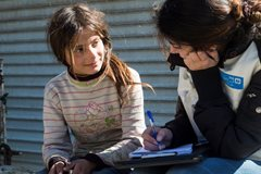 An SOS co-worker providing support to a young girl who was forced to leave her family home in Aleppo. She is no longer able to go to school – instead she spends her day searching for rubbish to sell (photo: SOS archives)