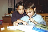 Girl helping her brother with his homework (Photo: SOS Archives)