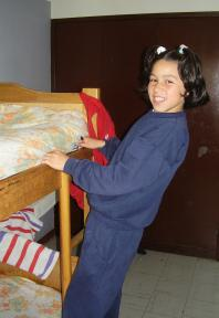A girl from Rubiela's family making her bed before leaving for school (Photo: SOS Archives)