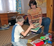 SOS mother Elena and six-year-old Danil clean the book shelf (Photo: M. Mägi)