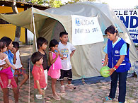 An SOS co-worker playing with children at the SOS day-care centre - Photo: F. Espinoza