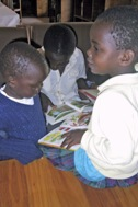 Three children reading a book (Photo: SOS Archives)
