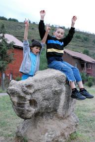 Boy and girl sitting outside waving - Photo: Katerina Ilievska