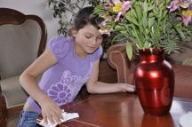 A girl from Rubiela's family dusting off a table (Photo: SOS Archives)